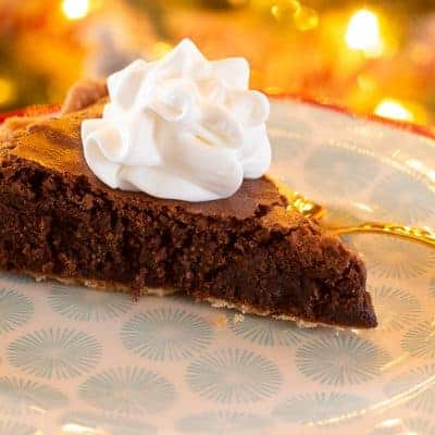 One slice of peppermint brownie pie on a Pioneer Woman plate topped with whipped cream and served with a gold fork
