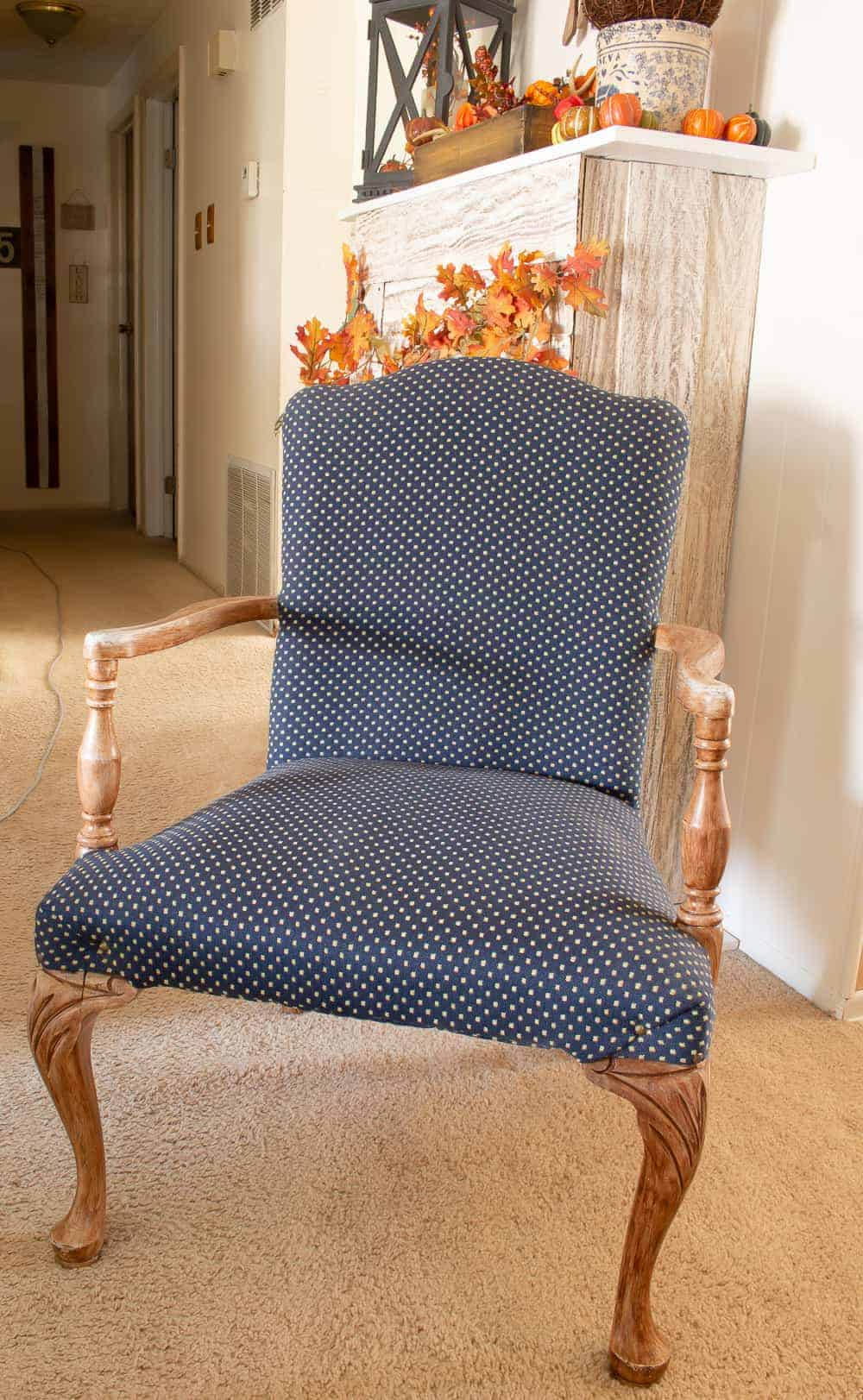 Antique chair with brown painted wood and blue and white fabric