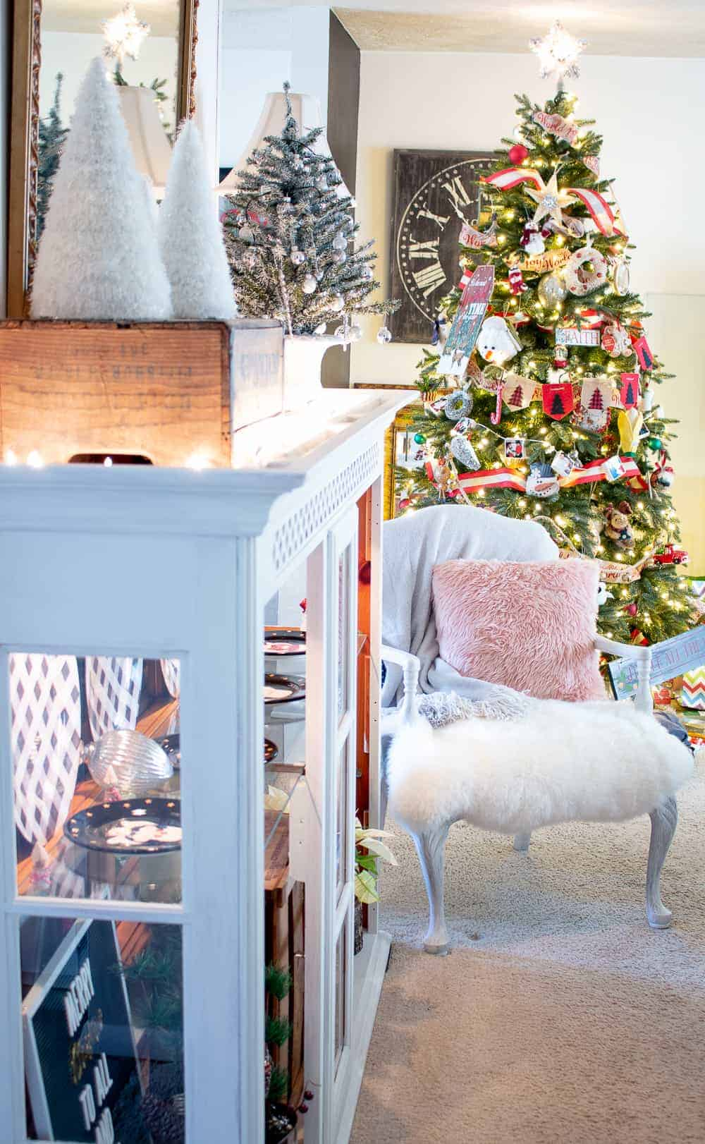 Old upholstered chair with wood trim painted white, covered with lamb's fur and a beautiful throw in front of a Christmas Tree