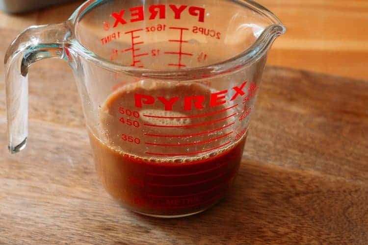 side view of homemade teriyaki sauce in a Pyrex glass measuring cup