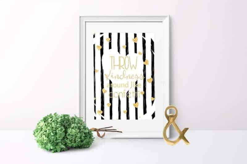 Throw Kindness Around Like Confetti - free printable shown in a white frame with a gold ampersand and bundle of dried green hydrangea on a white table with a white wall background