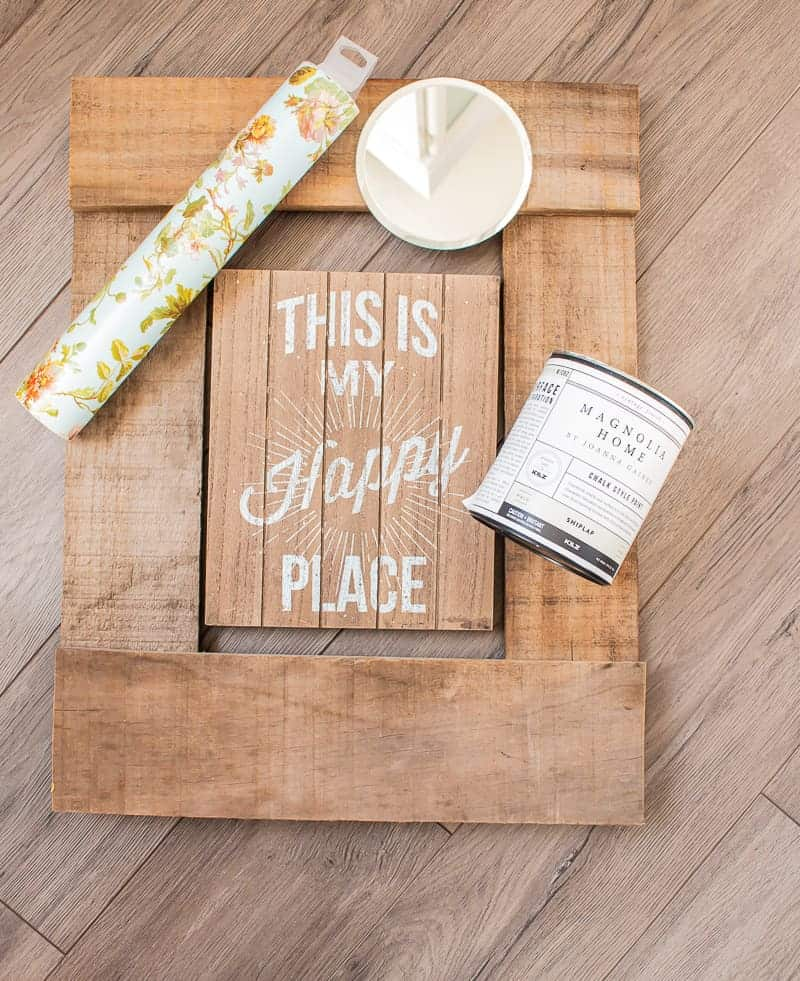 Overhead view of a frame made from deconstructed pallet wood with a wooden frame for repurposing inside, a can of Magnolia Home paint in shiplap color, a small mirror from the dollar store and patterned vinyl from Cricut.