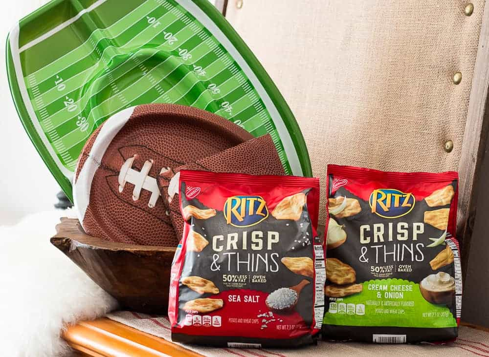 Two packages of RITZ Crisp & Thins with one opened package in a green serving bowl on a dresser with football paper plates in the background