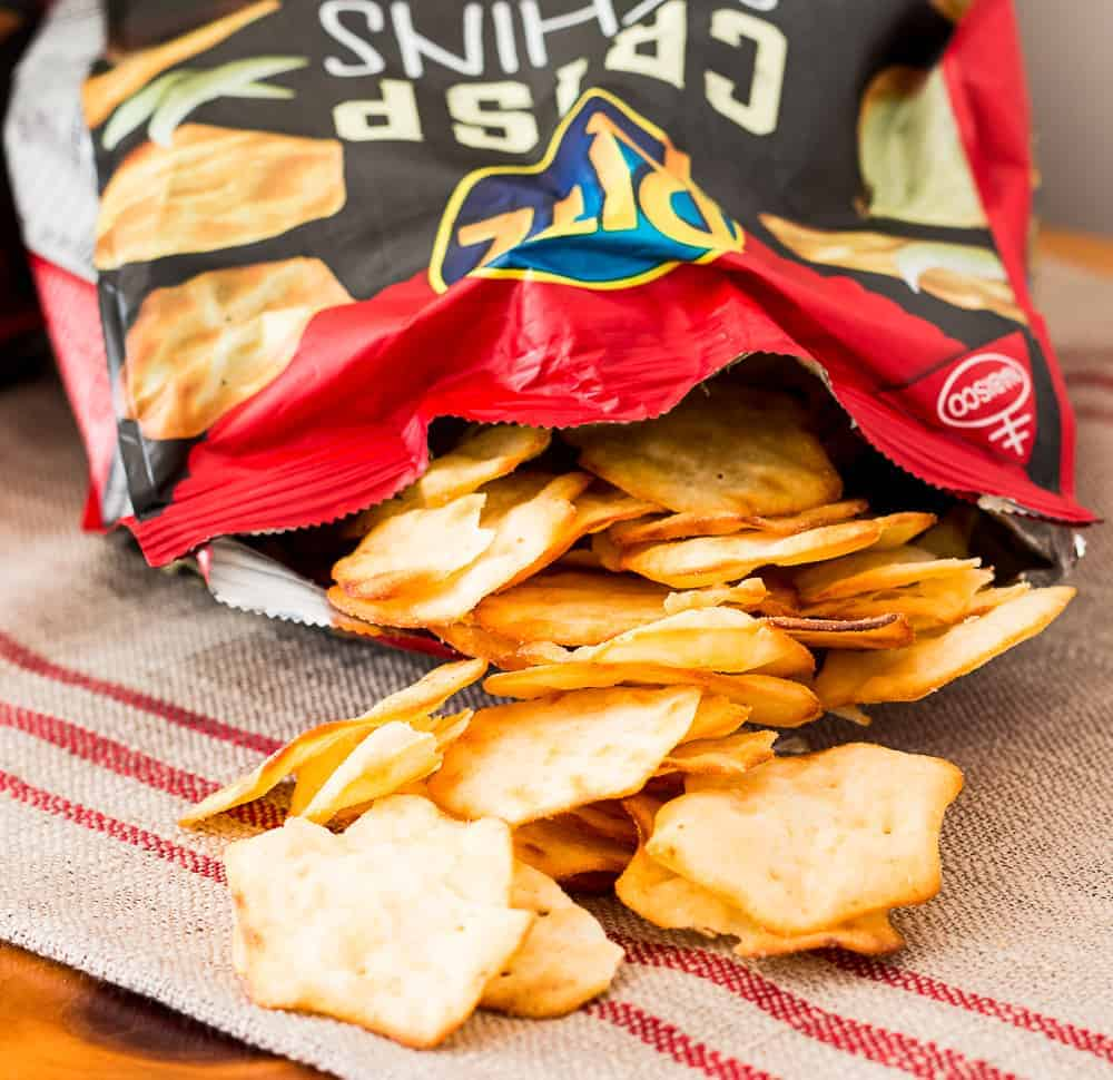 Two packages of RITZ Crisp & Thins with one opened packages and RITZ Crisp & Thins spilling out of package onto buffet