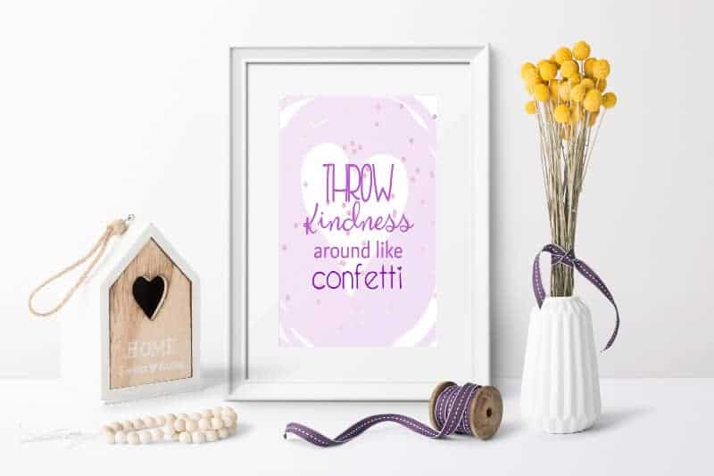 """Photo of a framed encouraging free printable that states, """"Throw Kindness Around Like Confetti"""" - white frame, spool of purple ribbon, birdhouse, and white vase filled with dried yellow flowers tied with purple ribbon"""