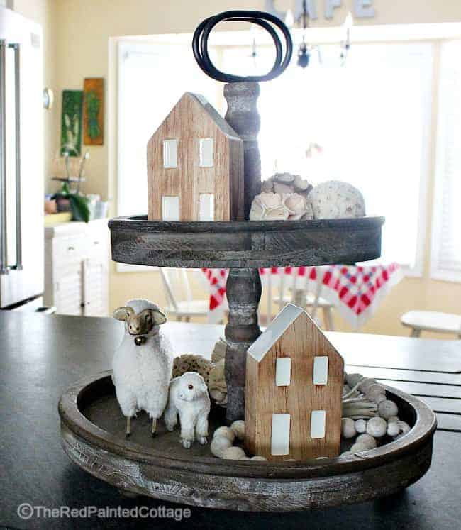 Farmhouse style tiered tray decorated for winter with lams and small wooden houses