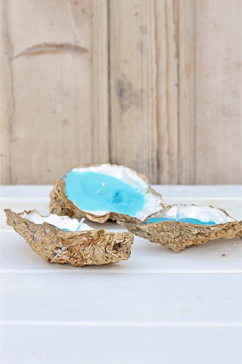 Gold spray painted oyster shells filled with ocean blue colored homemade candles