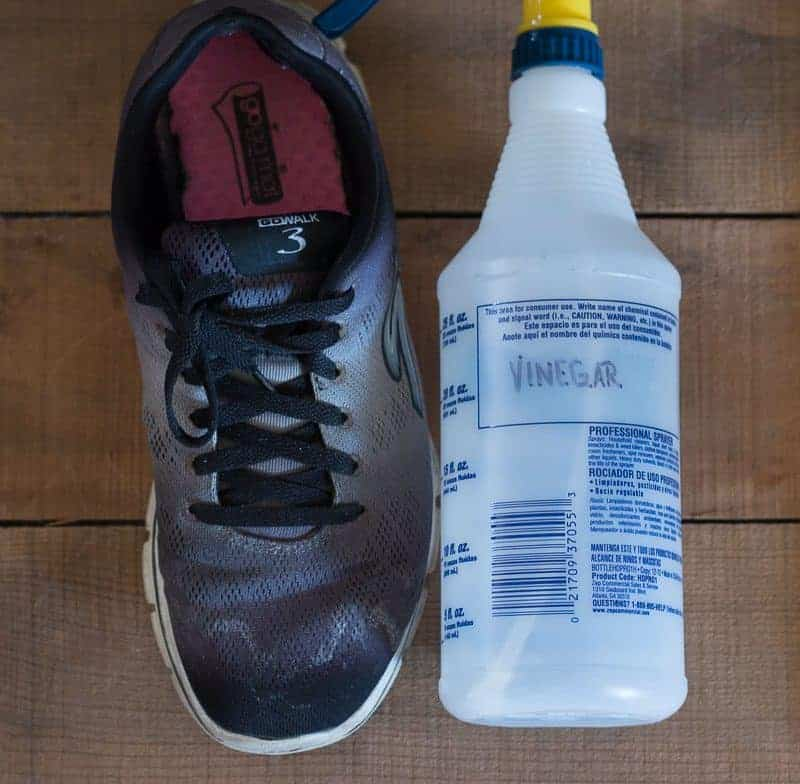 Vinegar spray bottle next to black salt stained tennis shoe