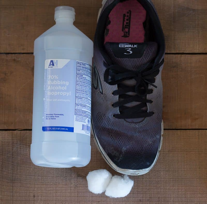 Household alcohol bottle and cotton balls next to salt stained black shoe - how to remove salt stains from shoes