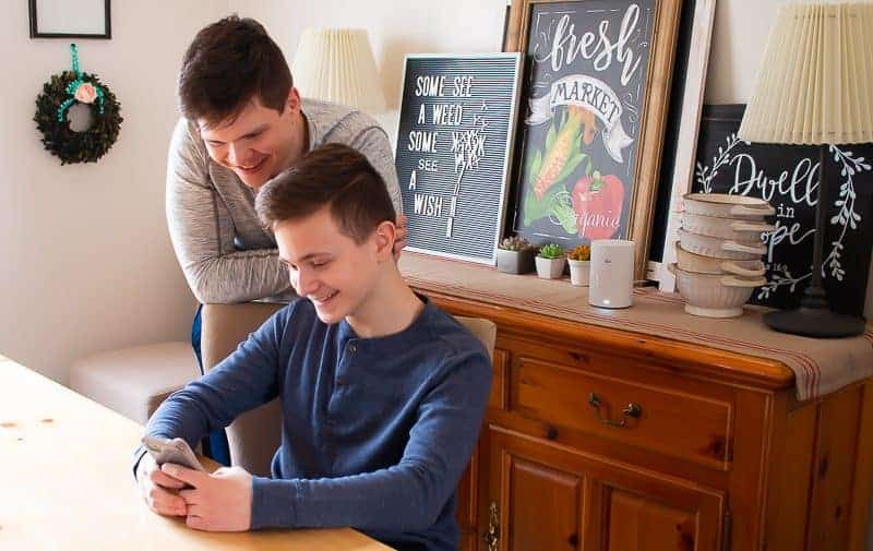 Photo of two boys smiling looking at pictures on a smartphone - how to organize photos