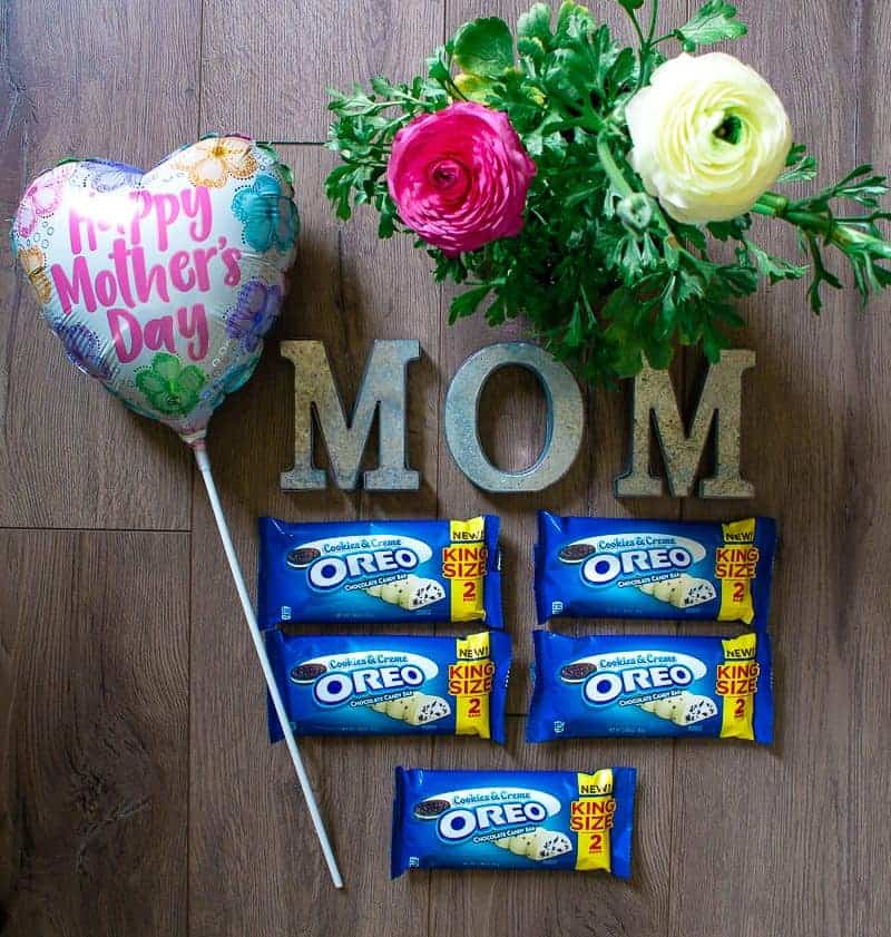 Overhead view of Mother's Day balloon, potted ranunculas, MOM spelled out in galvanized metal letters and 5 King Size Oreo Candy bars used to make a Mother's Day Candy Bar Bouquet