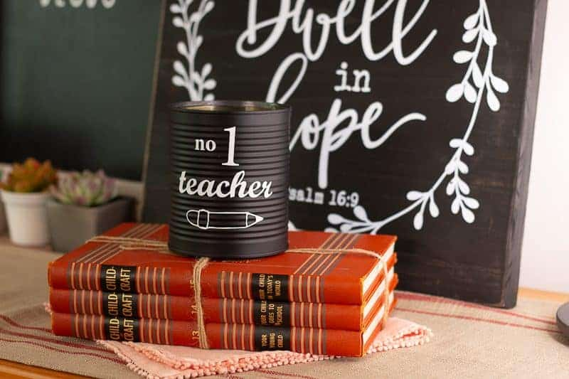 Spray painted black tin can with the phrase No. 1 teacher on the front in white vinyl.