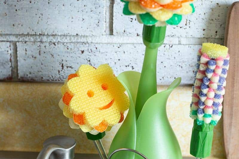 The cutest dishwand for cleaning dishes ever! The Scrub Daisy from Scrub Daddy on a stainless steel sink with farmhouse pig on white washed brick wall in the background
