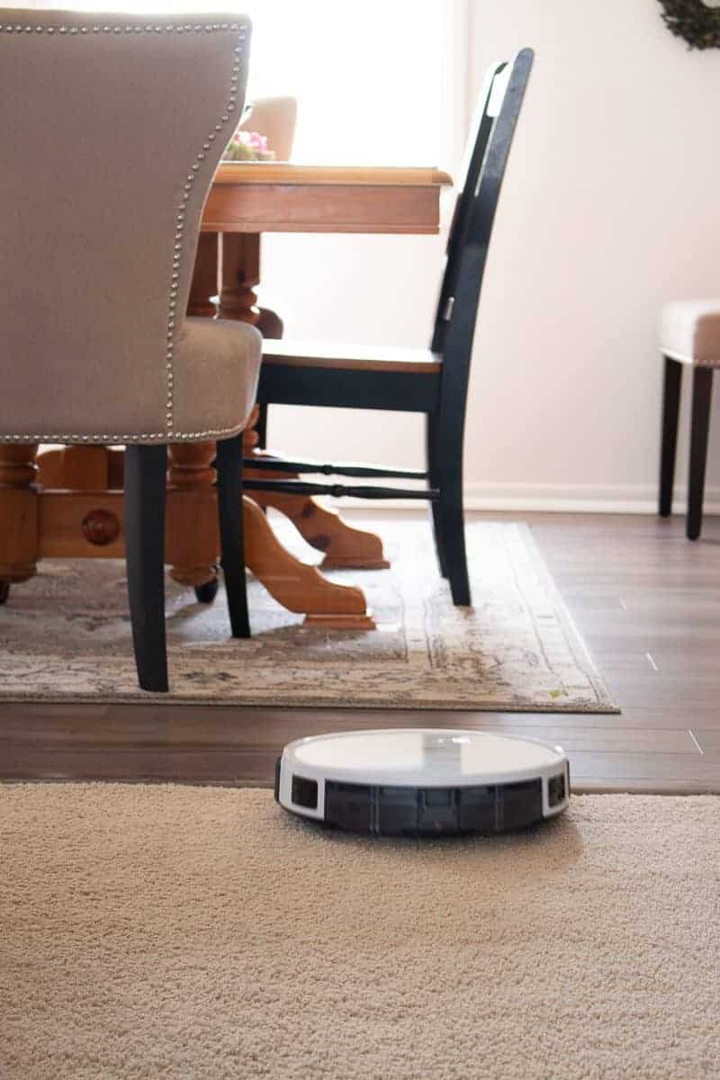 Photo showing a dining room table and chairs on a rug with farmhouse plank flooring showing a transition from carpeting to the flooring with a DEEBOT 600 robot vacuum working- Simple Time Saving Cleaning and Renovation Tips