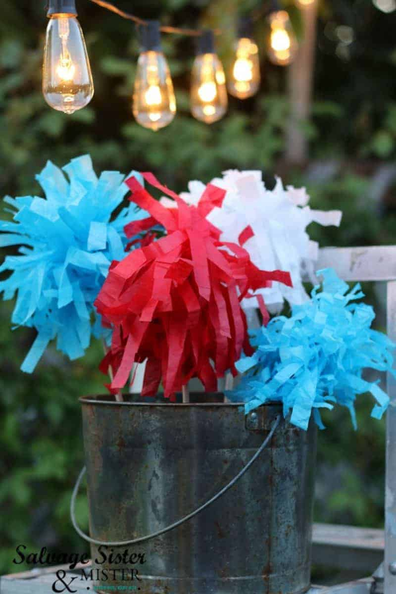 Galvanized bucket filled with tissue paper sparklers in red, white, and blue, perfect for a patriotic party