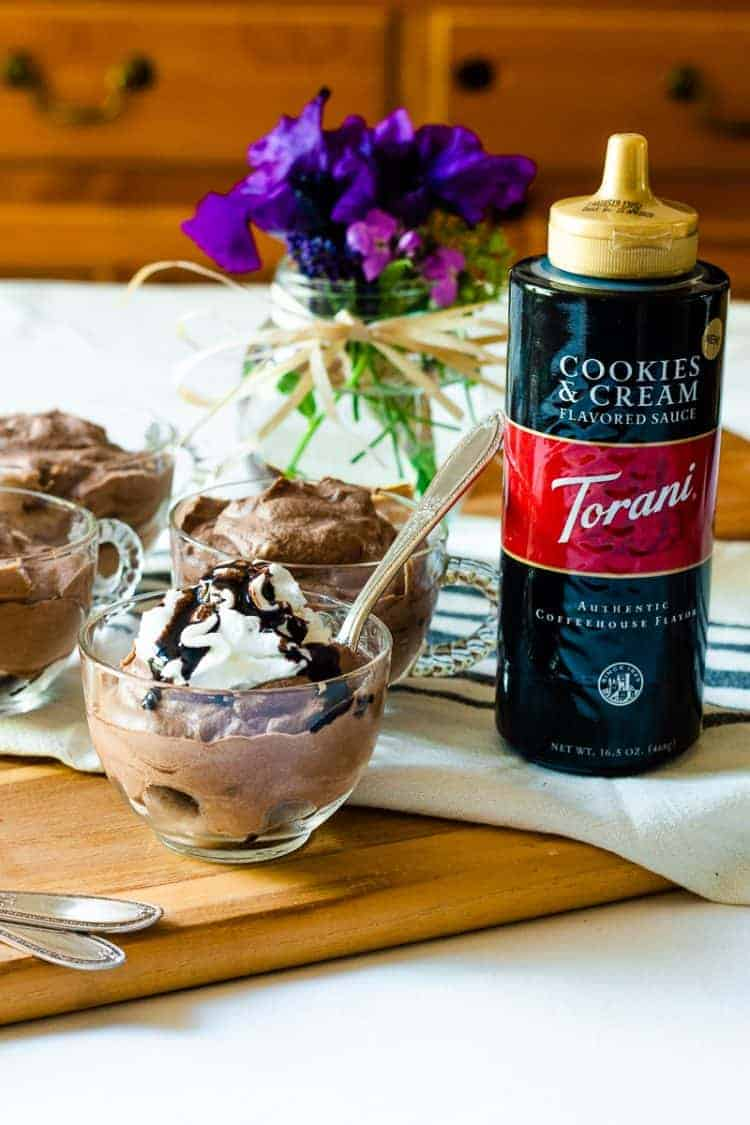 close up view of a cup of cookies and cream chocolate mousse with whipped cream and a drizzle of Torani Cookies & Cream syrup on top