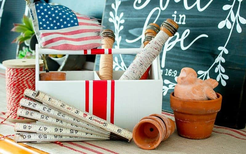 Front view of a white farmhouse tote with red grain sack stripes, vintage carpenter's rule, small American flag, weathered clay pots, and vintage wooden bobbins.
