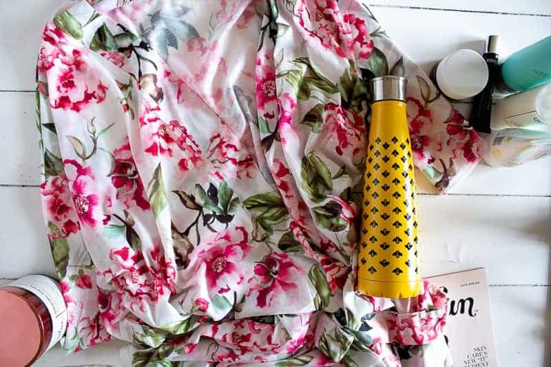 Overhead view of robe, mumu, from the Spring 2019 FabFitFun box and the Sip by Swell beverage holder with a yellow background and bumble bees