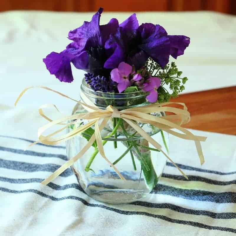Clear glass honey pot jar filled with purple flowers including a large purple iris, fresh lavender, and Dame's Rocket