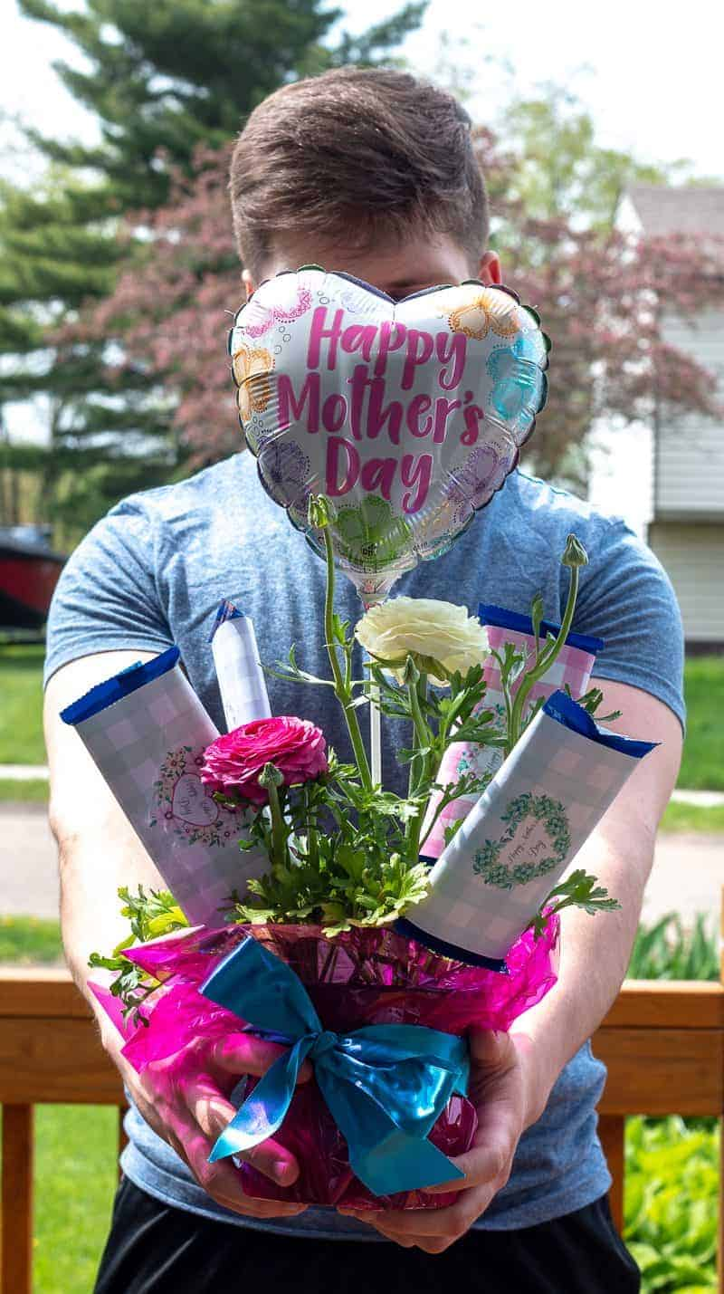 Young man holding a Mother's Day Candy Bar Bouquet
