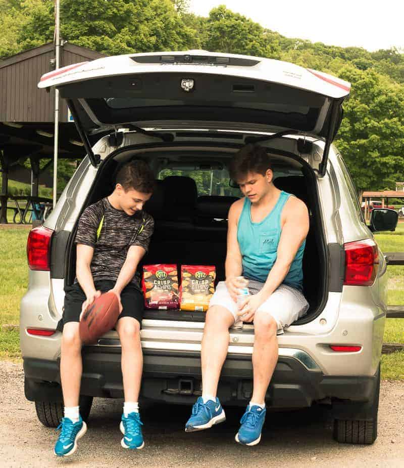 Two young men sitting in the hatchback of a car at a park