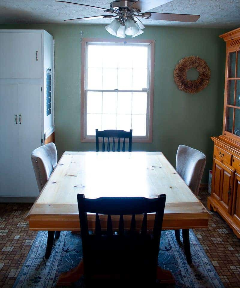 Kitchen facelift before picture - brown square linoleum floor and dining room table with large wooden pantry - the before of a cheap kitchen update