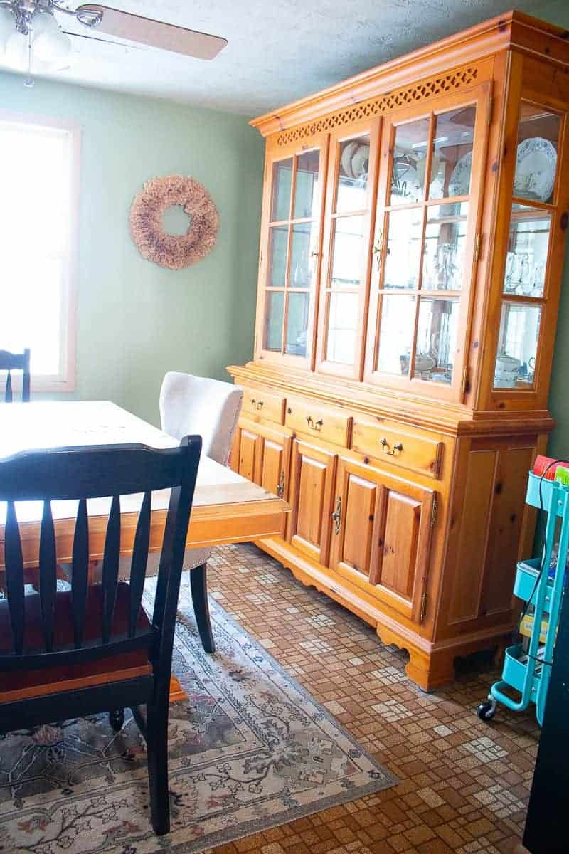 cheap kitchen update before photo of an old linoleum floor, a china cabinet and green walls - before an under $1000 Kitchen Makeover