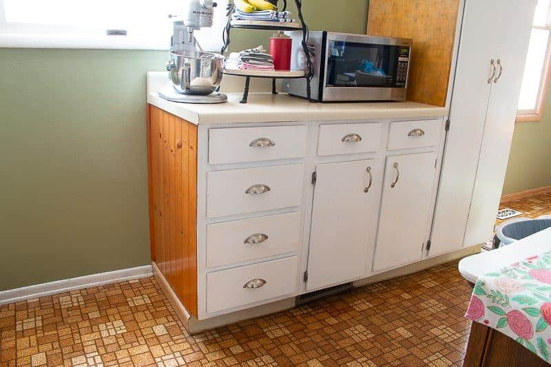 Cheap kitchen updates before photo of old flooring and wood kitchen cabinets and green walls - before pic of an under $1000 kitchen makeover