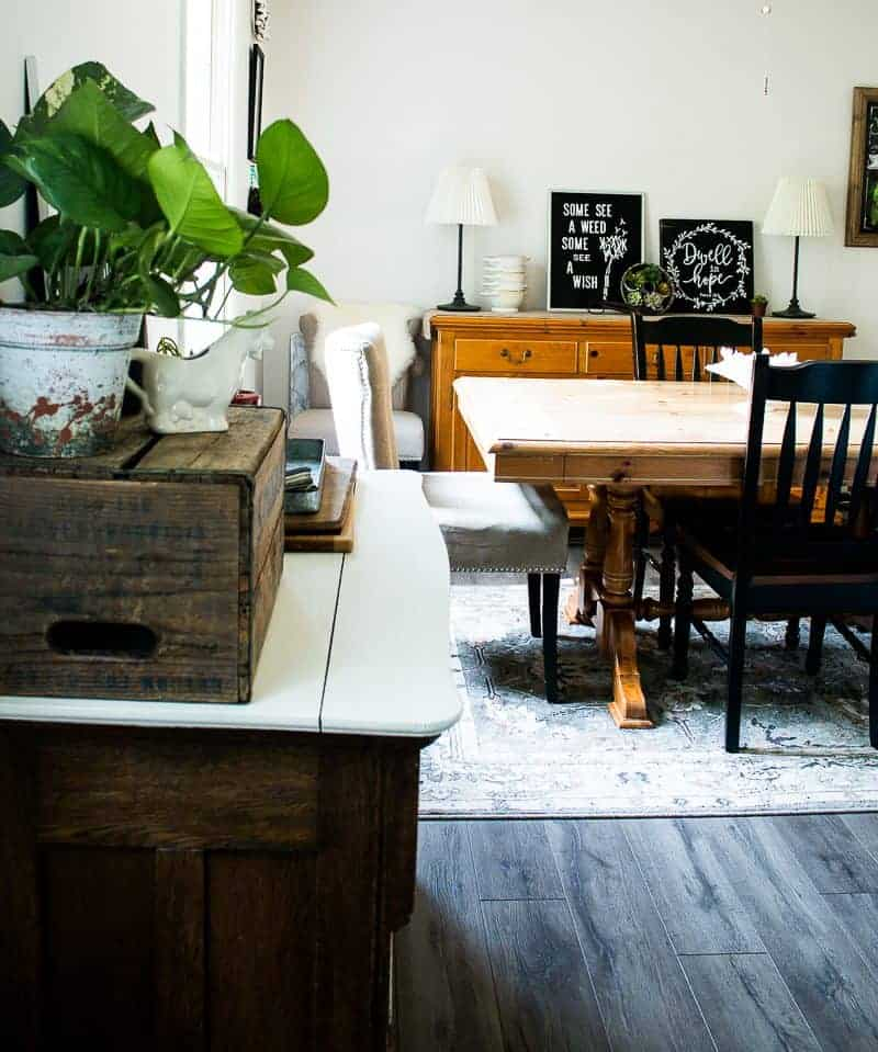after view of 1970's kitchen remodel, under $1000 kitchen makeover, showing grayish farmhouse plank laminate flooring that looks like hardwood flooring and freshly painted walls using Sherwin Williams Zurich White emerald