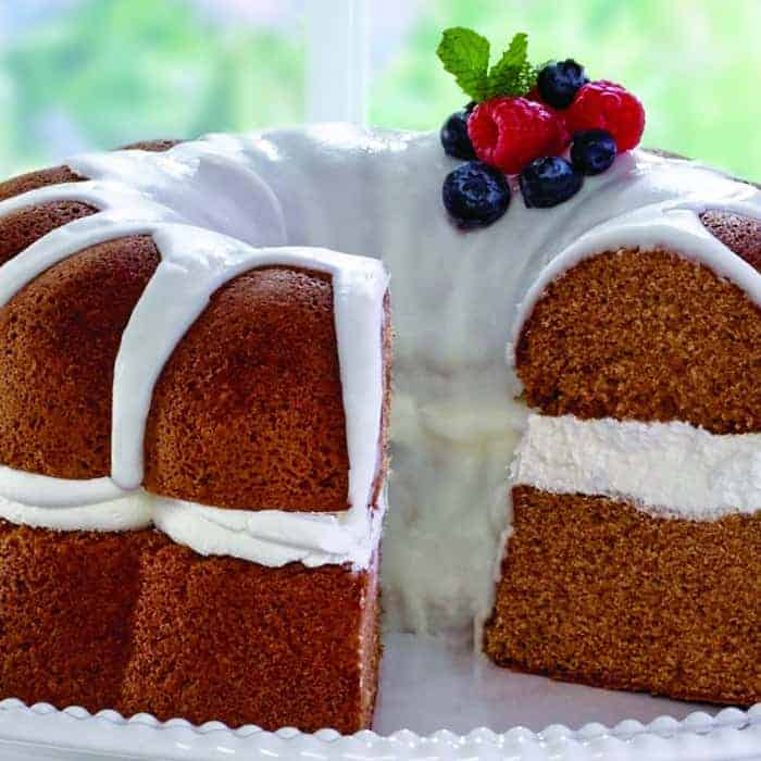 Lovely pound cake with white frosting, red raspberries, and blueberries - perfect Patriotic Party Food