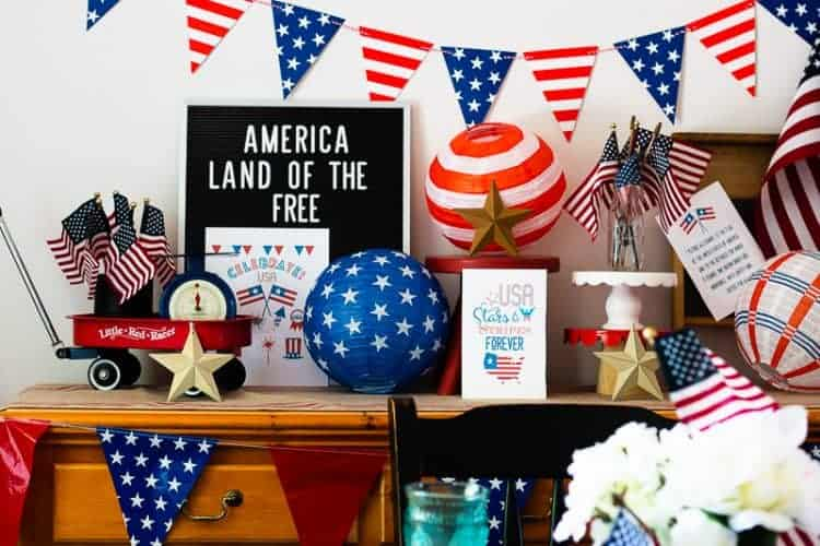 Buffet decorated for the 4th of July with a letterboard, banner, paper balls in red, white, and blue with stars and stripes, stacked cake stands with American Flags on them, a mini red flyer wagon filled with small American Flags and an antique blue scale and more