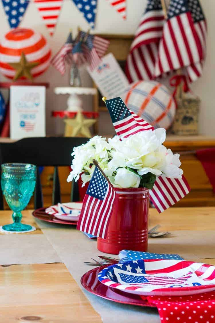 4th of July Placesetting with a red sugar canister centerpiece with faux flowers and small American flags with a 4th of July decorated buffet in the background
