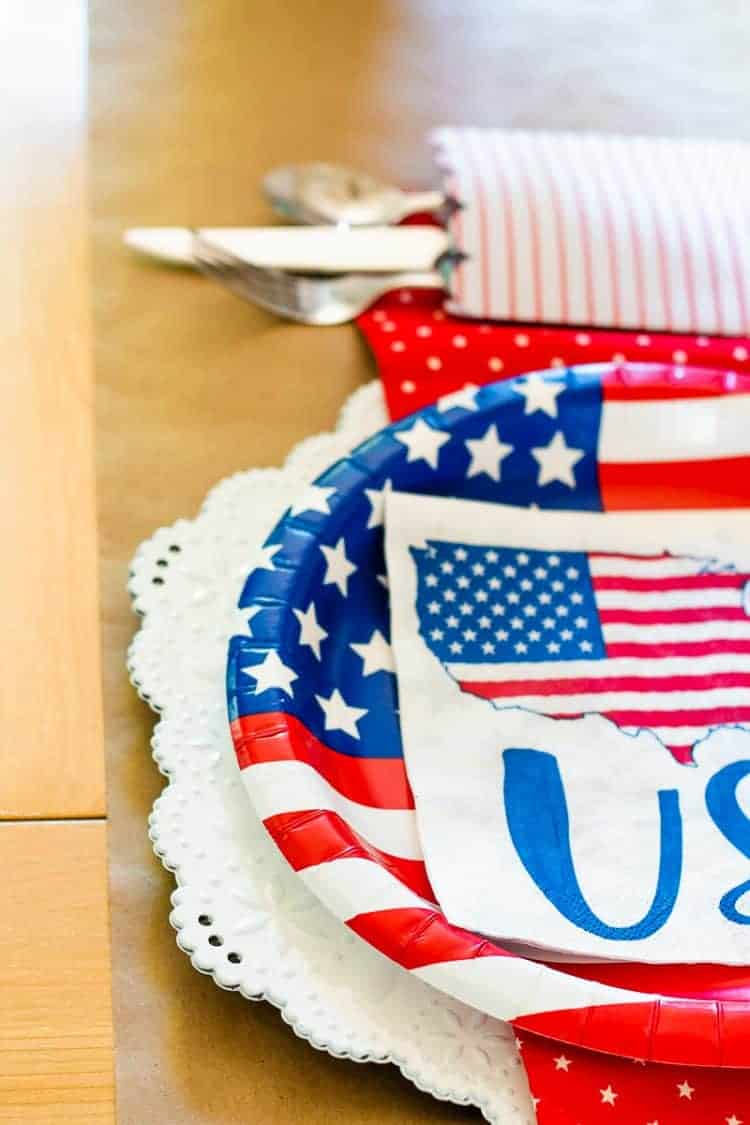 Close up view of 4th of July placesetting with paper plates and napkins from Walmart on a white plastic plate charger that looks like eyelet