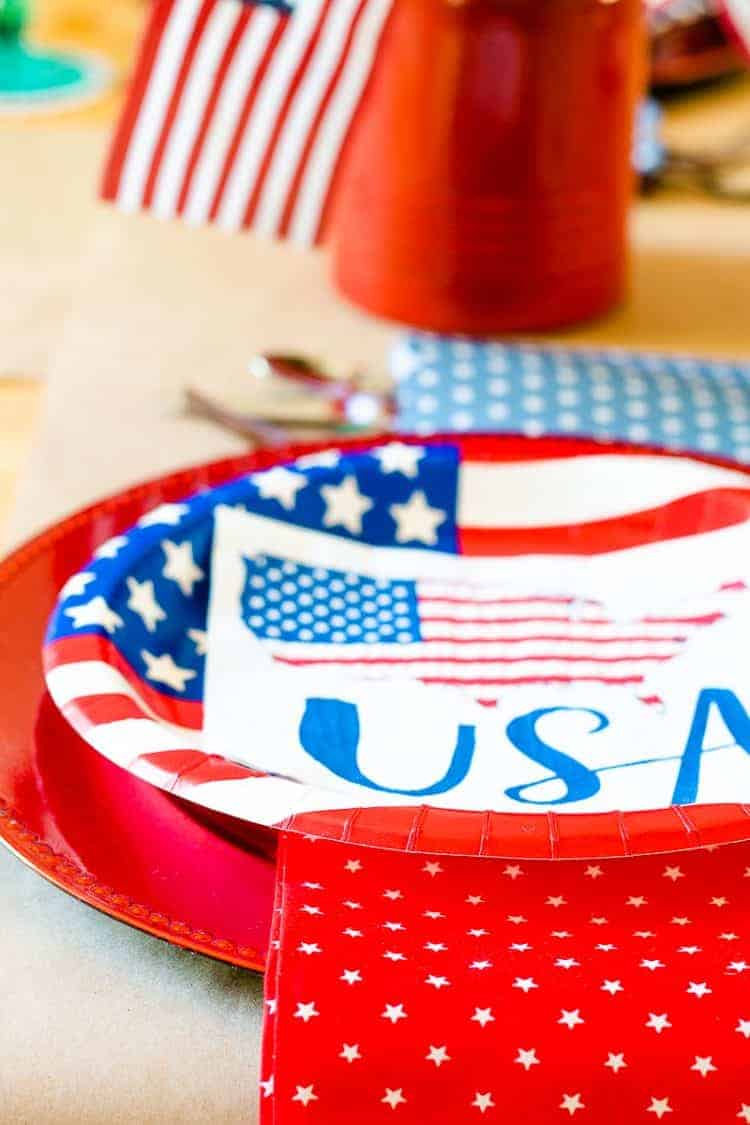 Close up view of 4th of July placesetting with paper plates and napkins from Walmart on a red plastic charger
