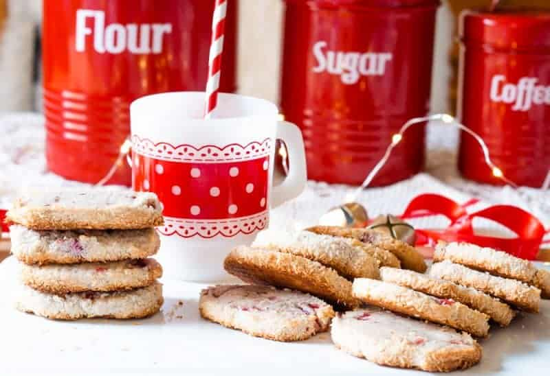 Front view of a stack of Santa's Whiskers Christmas Cookies in front of a vintage red and white firestone cup and 1950's red and white enamelware pantry canisters