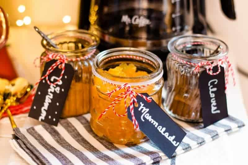 3 glass jars- one filled with ground cinnamon, one filled with ground cloves, and one filled with orange marmalade with chalkboard tags, red baker's twine, and chalkboard lettering