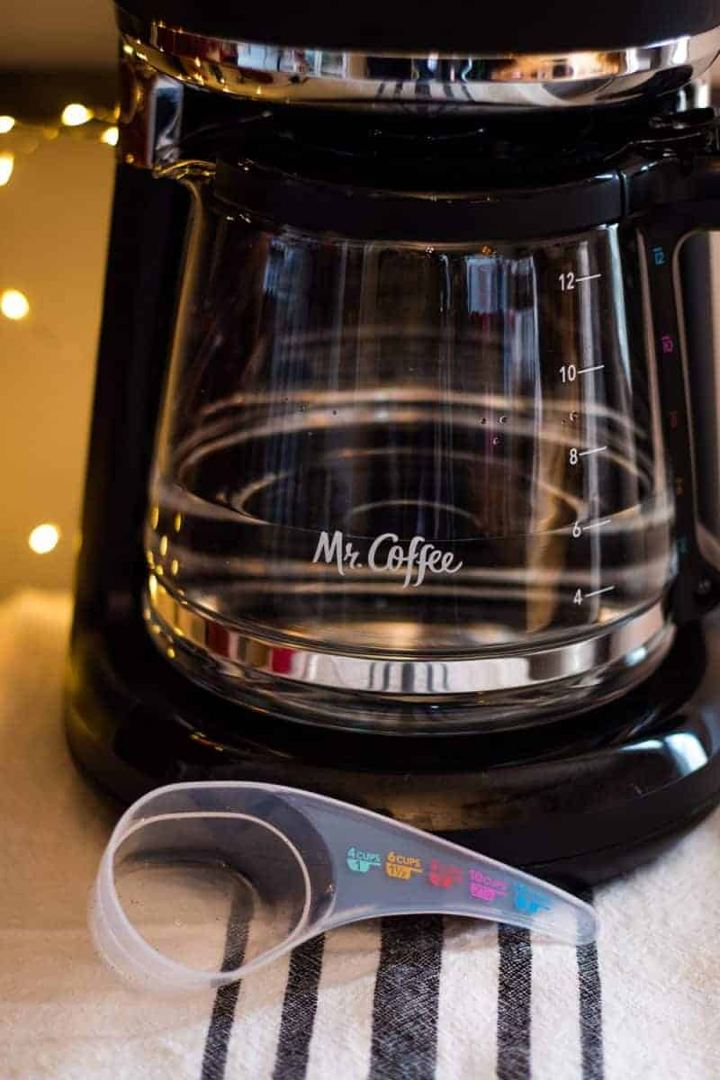 close up view of a Mr. Coffee glass carafe and a measuring scoop