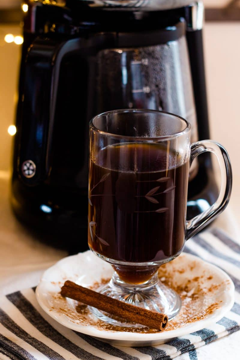 Fresh Christmas coffee in a glass coffee mug on a saucer with powdered sugar and a fresh cinnamon stick