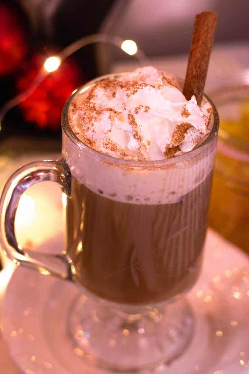 Overhead view of a cup of flavored coffee in a glass mug with whipped cream, sprinkled with cinnamon, and a cinnamon stick as a stirrer