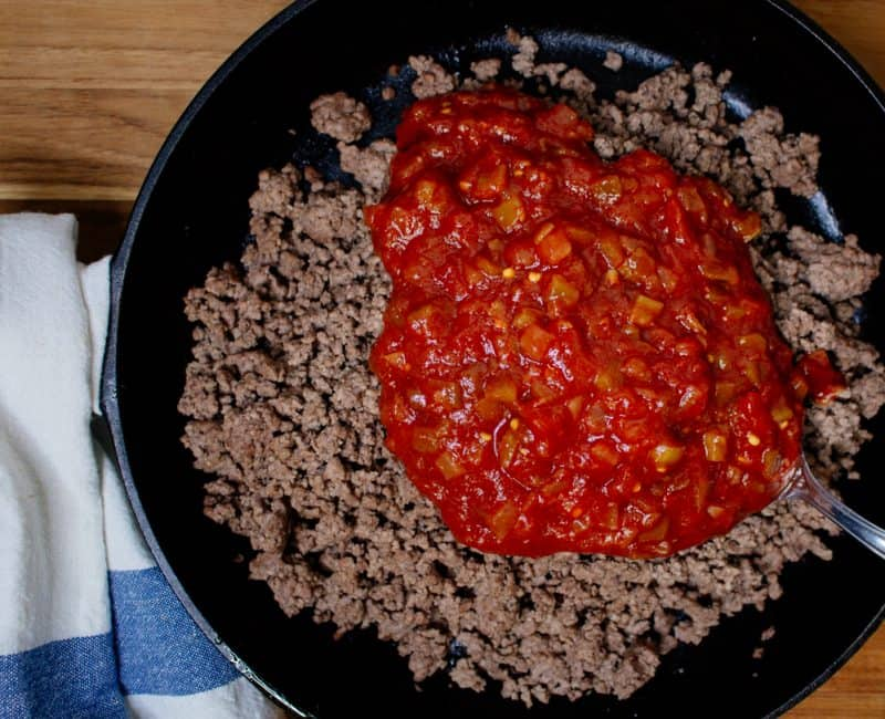 Ground beef in a cast iron skillet topped with salsa