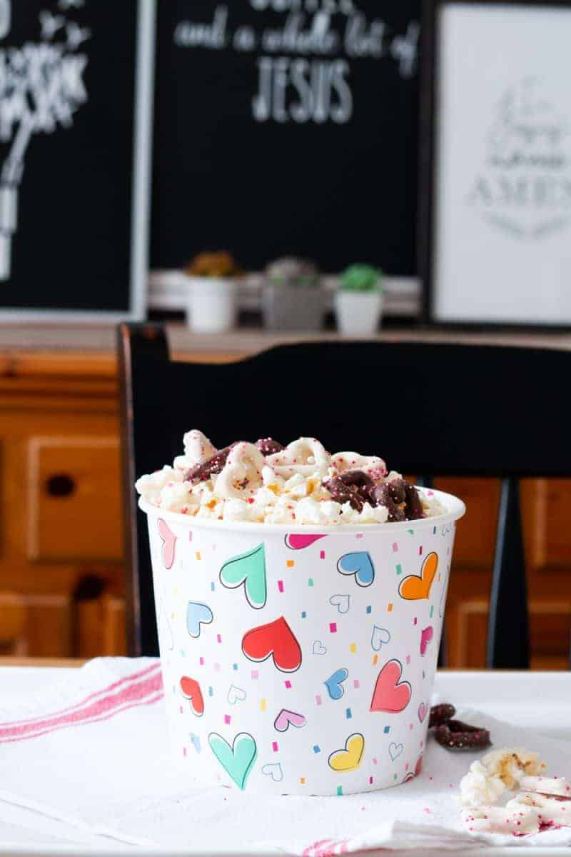 Popcorn pail with colorful hearts on it and filled with White Chocolate Popcorn