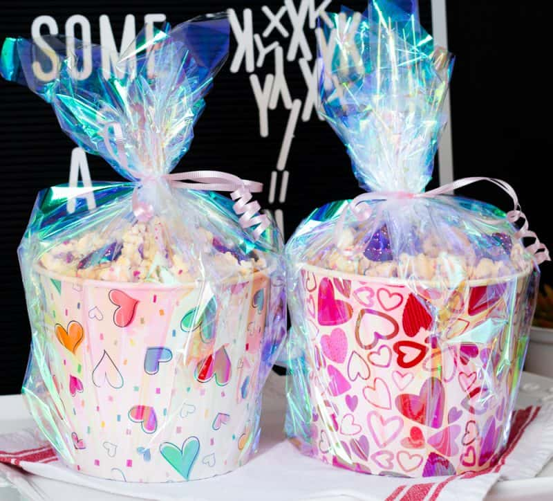 Two Valentine's Day Popcorn Pails filled with White Chocolate Popcorn and sealed in holographic saran wrap and tied with bows