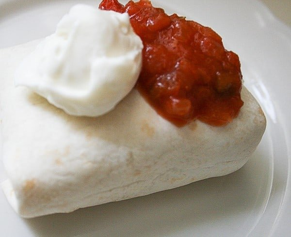 Make-ahead freezer burrito ready to serve with salsa and sour cream on top on a white plate
