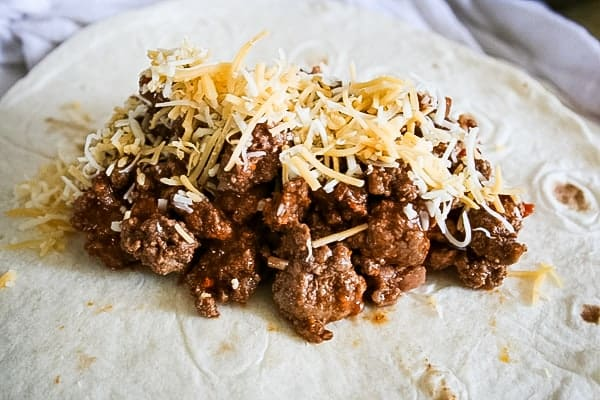 Meat mixture and cheese on a flour tortilla for make-ahead freezer burritos