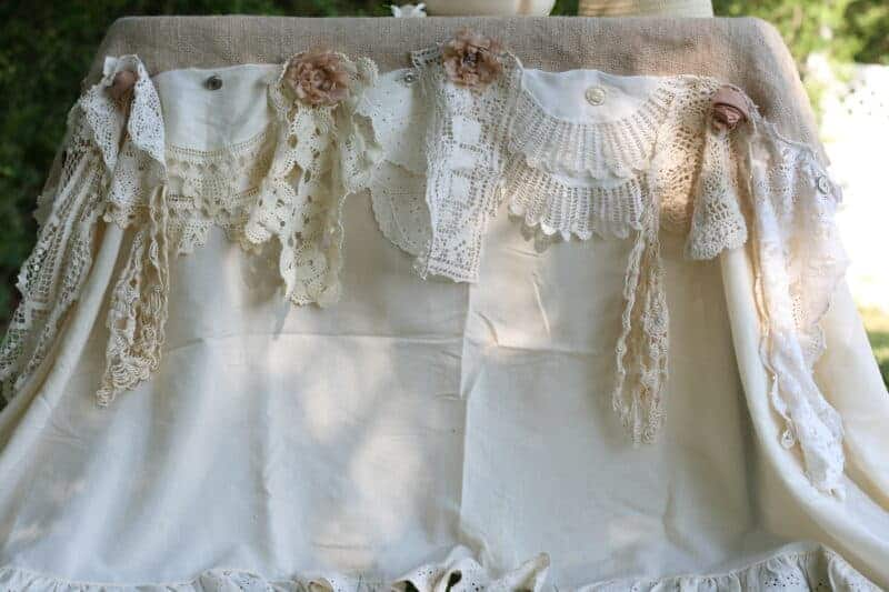 Outdoor romantic garden table setting using a ruffled bedsheet, burlap, and vintage doilies
