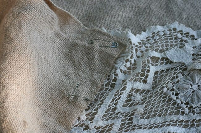Square of freshly laundered burlap with vintage doilies pinned to it to create a shabby chic tablecloth