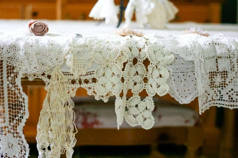 Vintage doilies layered on top of a square of burlap used to create a shabby chic tablecloth