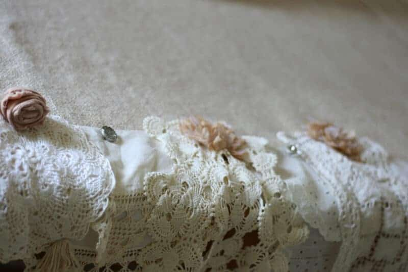 Burlap tablecloth with vintage linens pinned to it for a shabby chic tablecloth look