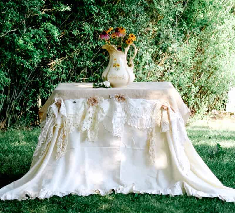 Outdoor romantic table covered with a ruffled sheet, freshly laundered burlap, and vintage linens to create a shabby chic tablecloth