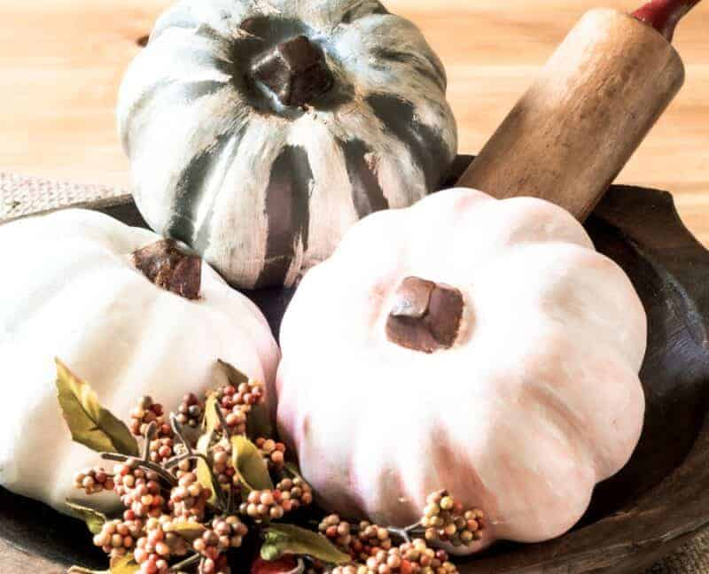 Painted dollar store pumpkins in a vintage dough bowl with an antique rolling pin.
